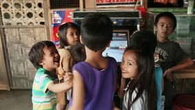 MANILA, PHILIPPINES - JANUARY 5, 2018: A group of gay Filipino children who gathered around a slot machine on the street stock footage