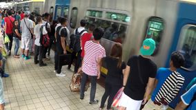 People wait for Arriving light rail train at station. Manila, Philippines - January 26, 2017: Passengers waiting for Arriving Light Rail Transit Train in stock video footage