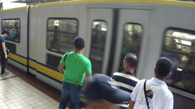 Light Railway Transit LRT passengers wait for the coming train. Manila, Philippines - July 9, 2017: Light Railway Transit LRT passengers waiting for the coming stock video footage