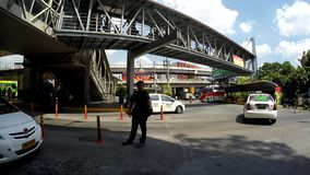 Private security guard managing traffic. Manila, Philippines - May 9, 2016: Private security guard managing traffic under metal overpass walkway stock footage