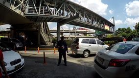 Private security guard managing traffic. Manila, Philippines - May 9, 2016: Private security guard managing traffic under metal overpass walkway stock video