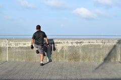 Matured man doing stretching exercise along ocean bay break water stock photos