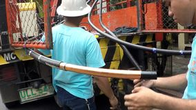 Huge electrical cable splicing and crimping. Manila, Philippines - September 23, 2016: Electrical workers splicing, stripping and crimping cap-in huge cable wire stock video footage
