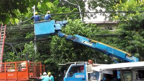 Electrical workers on telehandler with bucket. Manila, Philippines - September 23, 2016: Electrical workers on telehandler with bucket crane install huge cable stock video