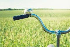 Manillar del vintage con la campana en la bicicleta Día de verano para el viaje Vista del campo de trigo outdoor primer foto de archivo libre de regalías