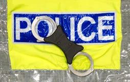 Manillas de la policía en hola una chaqueta visibilty Foto de archivo libre de regalías
