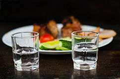 Manimals. Still life with two glasses and plate with meat on the background Stock Images