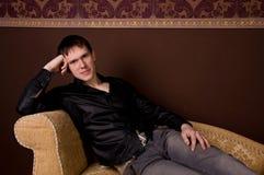 Manin casuale che si siede sul sofà Fotografia Stock Libera da Diritti