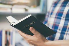 Maninnehav och läsning den heliga Christian Bible royaltyfri fotografi