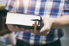 Maninnehav och läsning den heliga Christian Bible royaltyfria bilder