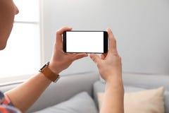 Maninnehavsmartphone med den tomma skärmen, closeup av händer Utrymme f?r text arkivbilder