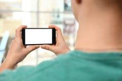 Maninnehavsmartphone med den tomma skärmen, closeup av händer Utrymme f?r text royaltyfria bilder