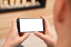 Maninnehavsmartphone med den tomma skärmen inomhus, closeup av händer royaltyfri foto