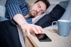 Maninnehavsmartphone som ligger i hans säng royaltyfri bild