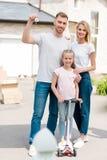 maninnehavtangent med billiga prydnadssaken medan hans fru som framme omfamnar dottern på sparksparkcykeln av nytt royaltyfri fotografi