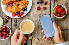 Maninnehavtelefon och kopp kaffe Royaltyfri Foto