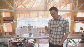 Maninnehavtelefon som smsar under avbrott inom kontor lager videofilmer