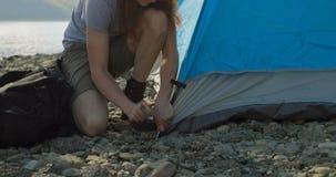 Maninställning - upp tältet nära flodstranden 4k arkivfilmer