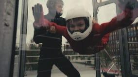 Maninstruktören undervisar en kvinna att flyga in i vindtunnelen Inomhus himmeldykning stock video