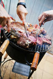 Manipulant et coupant la viande de barbecue Images libres de droits