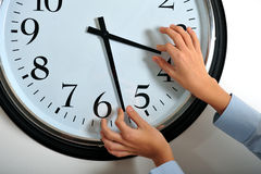 Manipulating time. Business man hands manipulating hands of clock Royalty Free Stock Images