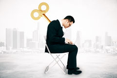 Manipulation concept. Businessman with wind up key on his back sitting on chair and using laptop computer on city background. Manipulation concept Royalty Free Stock Image