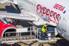 Manipulation de l'agent déchargeant un avion exprès d'Ibérie à l'aéroport de Berlin Tegel Photographie stock