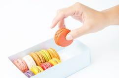 Manipule le macaron dans la boîte sur le fond blanc Photos stock