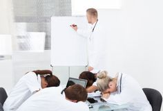 Manipulera att ge presentation till kollegor som sover på skrivbordet fotografering för bildbyråer