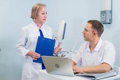 Manipulera att ha konversation med hans kollega i medicinskt kontor royaltyfri bild