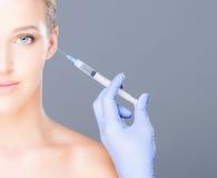 Manipulera att injicera botox i en härlig framsida av en ung kvinna fotografering för bildbyråer