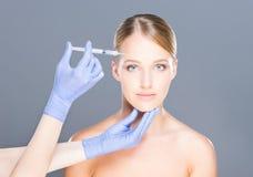 Manipulera att injicera botox in i framsida av en ung kvinna Arkivbild