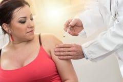 Manipulera att injicera vaccinen till den unga kvinnan, ljus effekt Royaltyfria Bilder