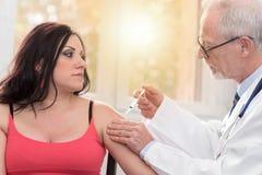 Manipulera att injicera vaccinen till den unga kvinnan, ljus effekt Royaltyfri Foto