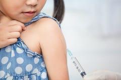 Manipulera att injicera vaccinering i arm av den asiatiska flickan för det lilla barnet Royaltyfri Bild
