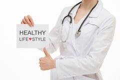 Manipulera att kalla till den sunda livsstilen och uppvisning av tummen upp tecken Royaltyfria Bilder