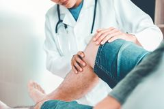 Manipulera att konsultera med tålmodig knäproblemsjukgymnastik Co royaltyfria bilder