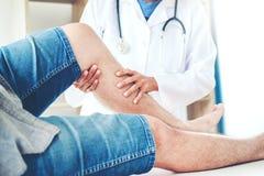 Manipulera att konsultera med tålmodig knäproblemsjukgymnastik Co royaltyfri bild