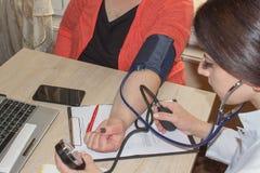 Manipulera att kontrollera blodtryck av en patient, honom mäter hea Royaltyfria Bilder