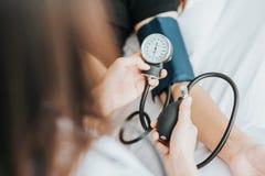 Manipulera att kontrollera blodtryck av en patient med sphygmomanometeren Arkivbild