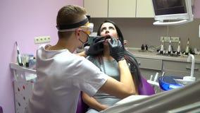 Manipulera att kontrollera tänderna av patienten för a-brunettkvinnan i tand- klinik: hyra rum med rosa väggar och purpurfärgad t stock video