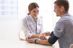 Manipulera att kontrollera tålmodigt blodtryck för ` s i sjukhus royaltyfri foto