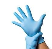 Manipulera att sätta på skyddande handskar som isoleras på vit Royaltyfri Bild