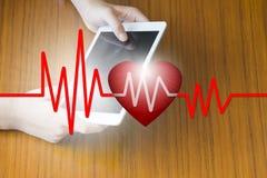 Manipulera den hållande minnestavlan med hjärtatakten, E-hälsa begreppet, affärsidéen, affärsidé Arkivfoto