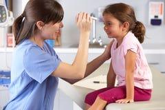 Manipulera det undersökande barnet synar i doktors Kontor Arkivbild