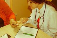 Manipulera diskutera rekord med hög kvinnlig tålmodig doctor tålmodign Arkivbild