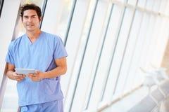 Manipulera genom att använda den Digital tableten i korridor av det moderna sjukhuset royaltyfri bild