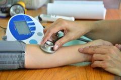 Manipulera genom att använda stetoskopet med patienten för har en kontroll-upp royaltyfri fotografi