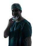 Manipulera kirurgmanståenden med framsidamaskeringen som ler vänlig silh Royaltyfri Bild