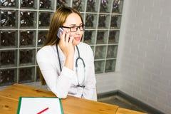 Manipulera kvinnan i medicinskt kontor som ler och talar på telefonen Royaltyfri Foto